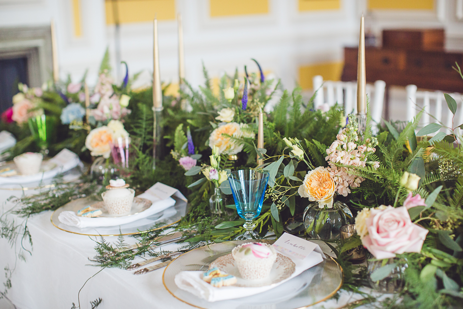 A cute cupcake & cookie table favour with beautiful gold and glass chargers mix with fresh foliage in our dramatic table runner