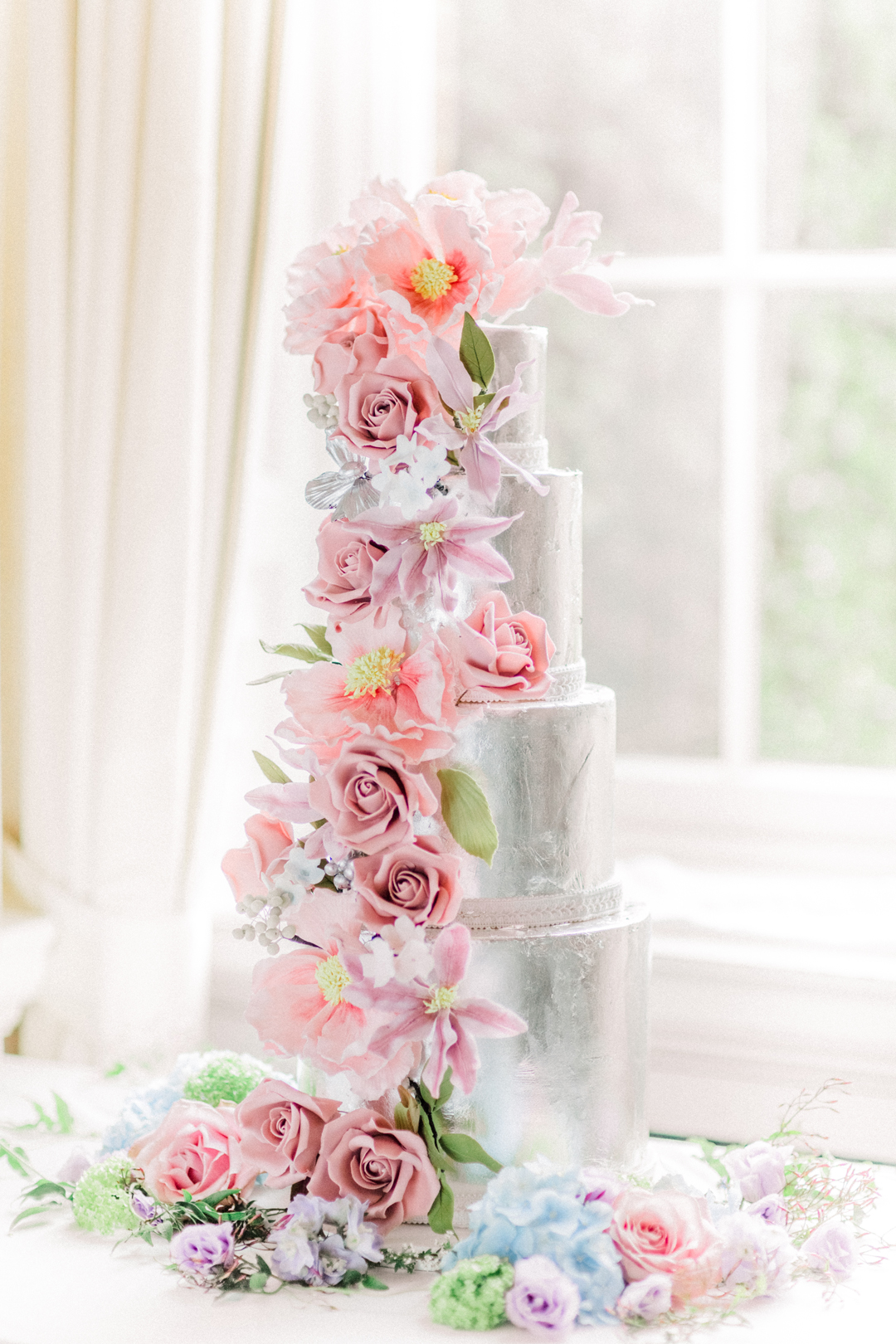 For a show stopping piece this all silver 4 tiered cake with gorgeous pink sugar flowers is the perfect colour combination. Cake by Elizabeth's Cake Emporium. Image: Sanshine Photography