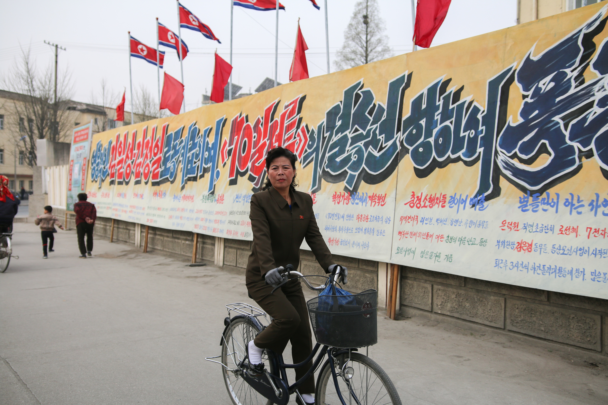 A woman rides past a a sign exhorting victory in the 70 day battle in Kaesong.  Photo by Joe Han