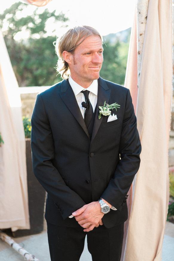 Groom seeing bride walk down aisle