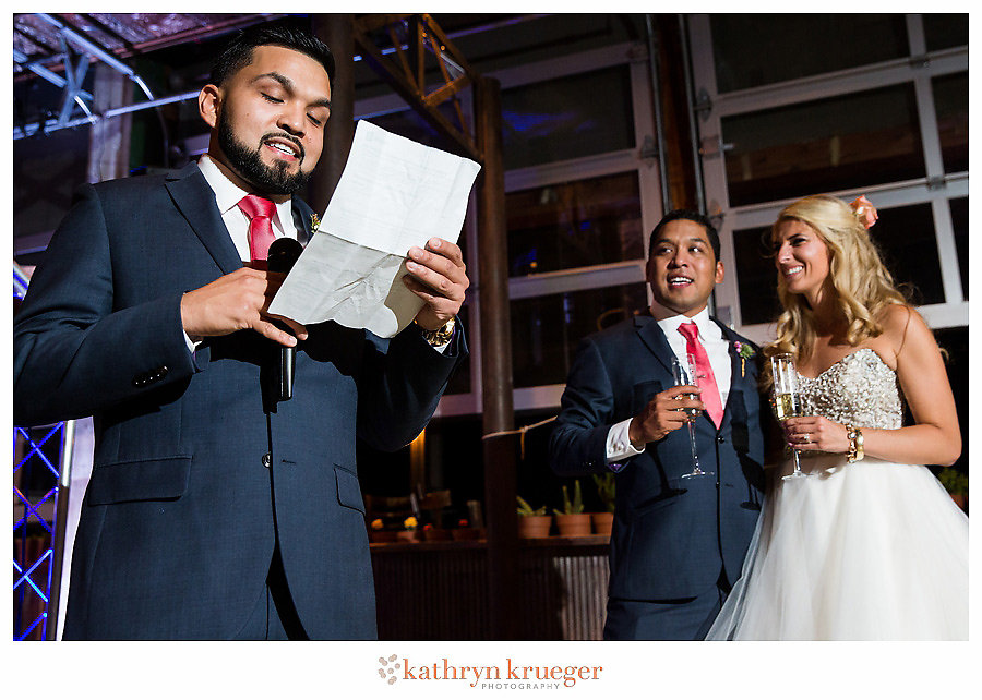Best man toasting; couple looking on