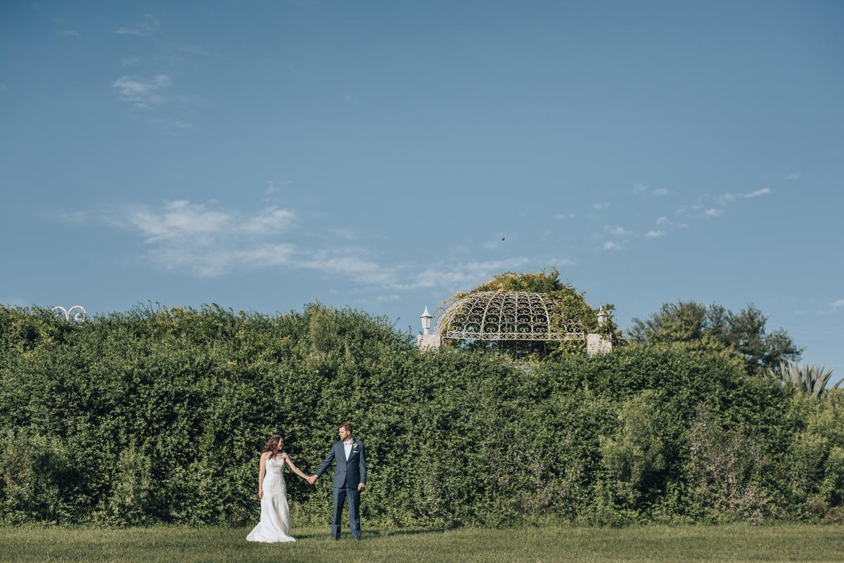 Bride and groom Vintage Villas arbor in background