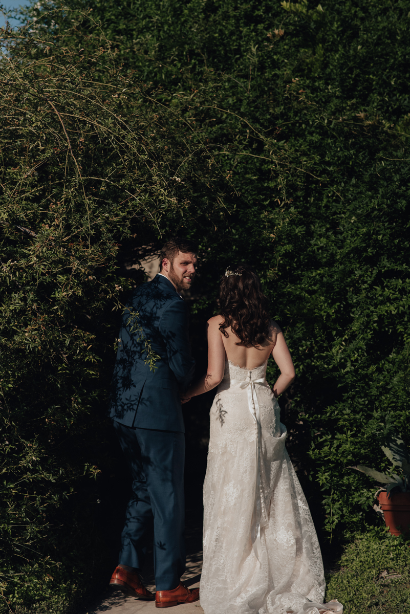 Bride and groom sneaking into bushes