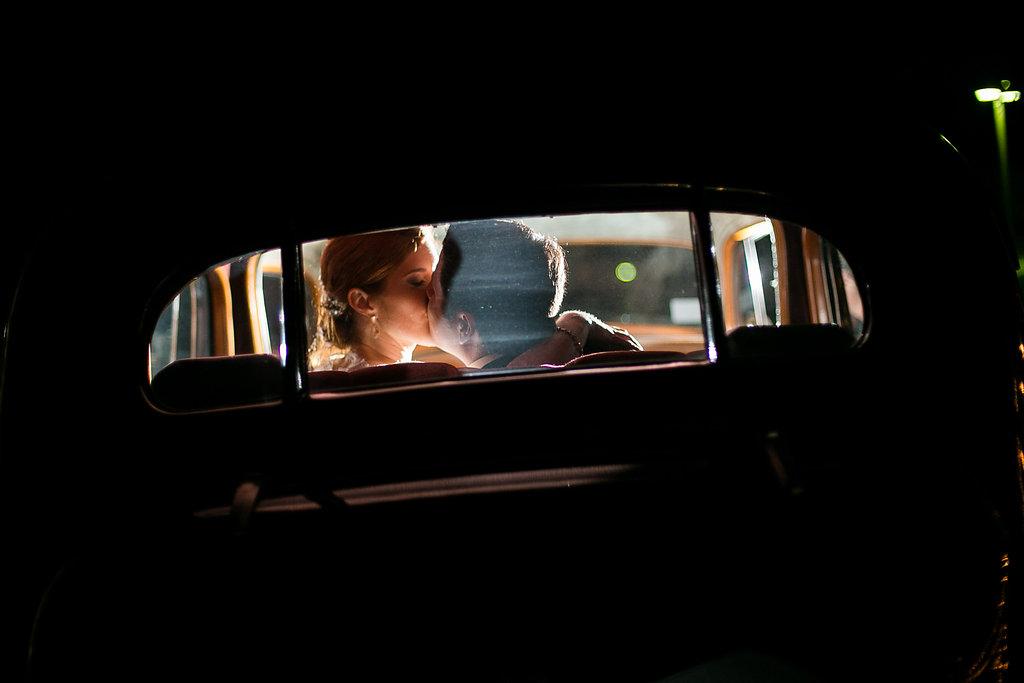 Bride & groom kissing in getaway car