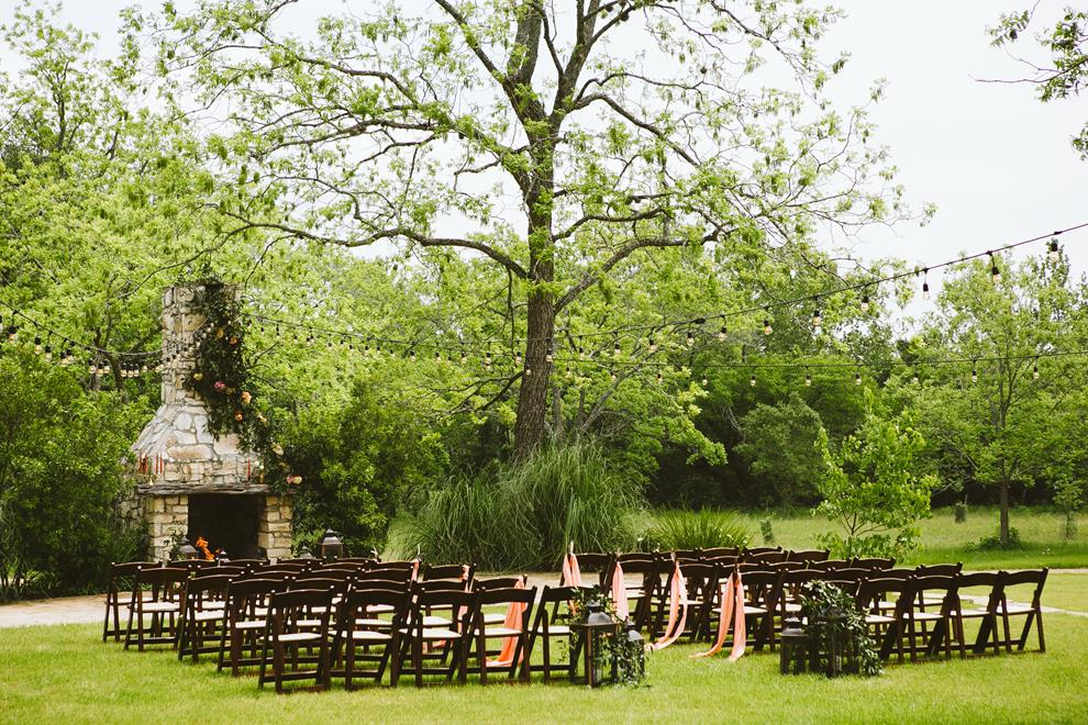 Pecan Springs Ranch fireplace ceremony setup; scarves on chairs; cafe lights
