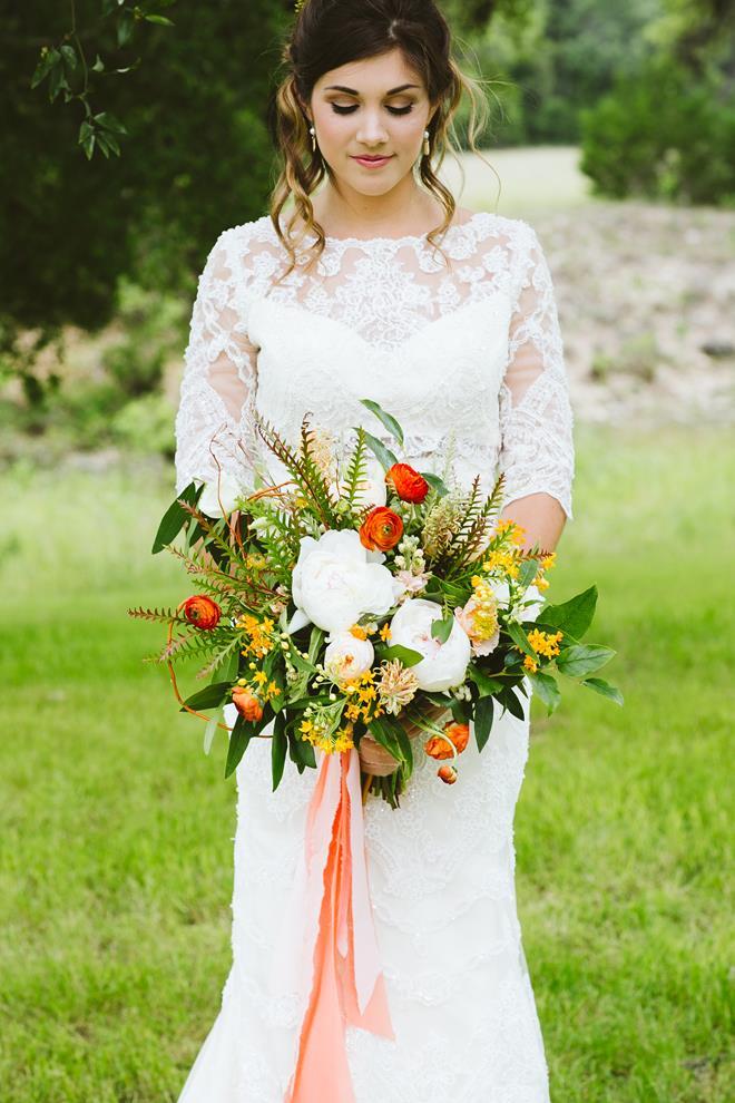 Bride with orange peach green bridal bouquet