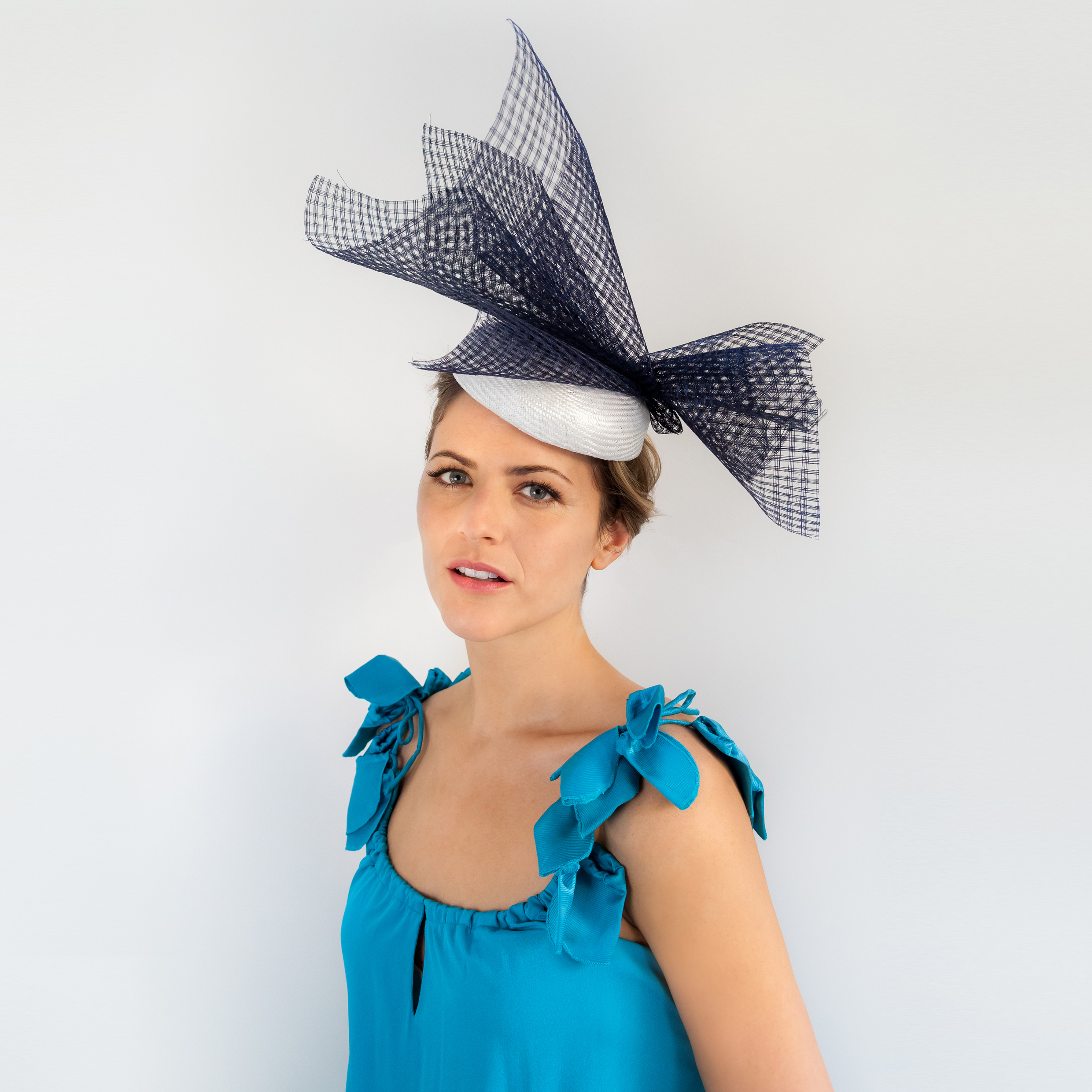 ABSTRACT - £60  White straw button headpiece with navy pierced straw spray.