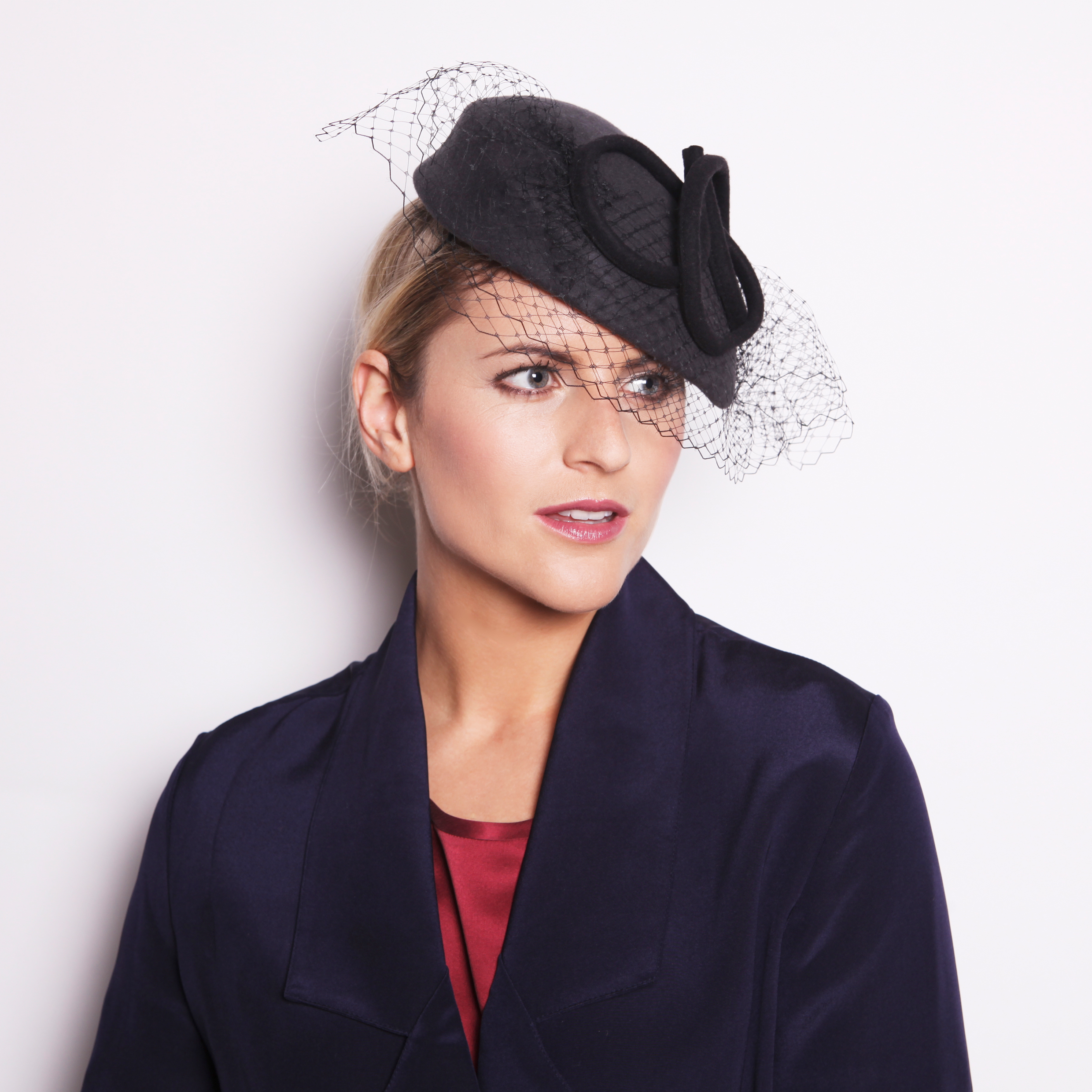 AILE - £75  Grey wool felt oval headpiece with black loops and black veiling.