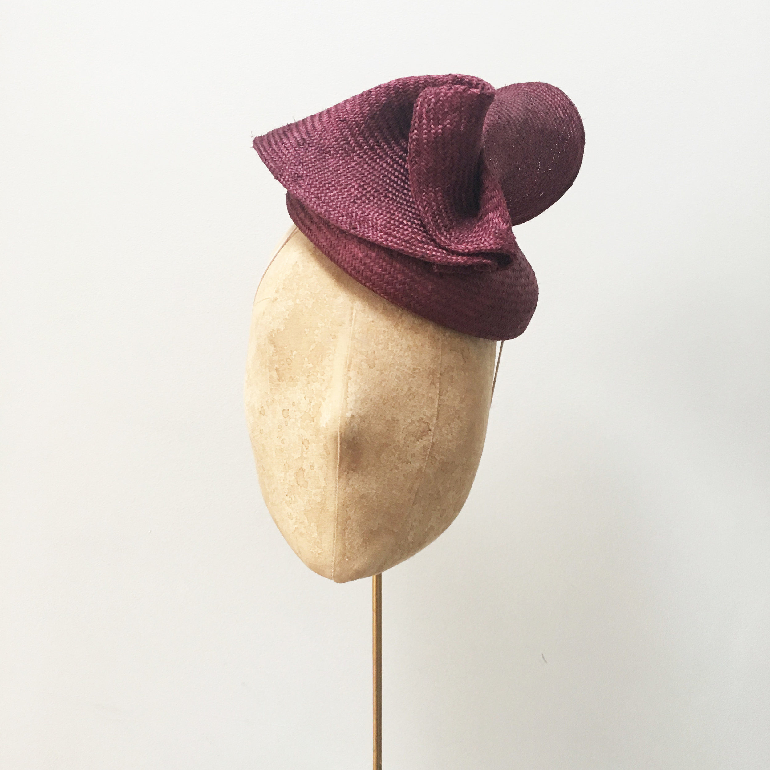 SCROLL - £60  Maroon sisal straw button headpiece with matching soft structural folds.