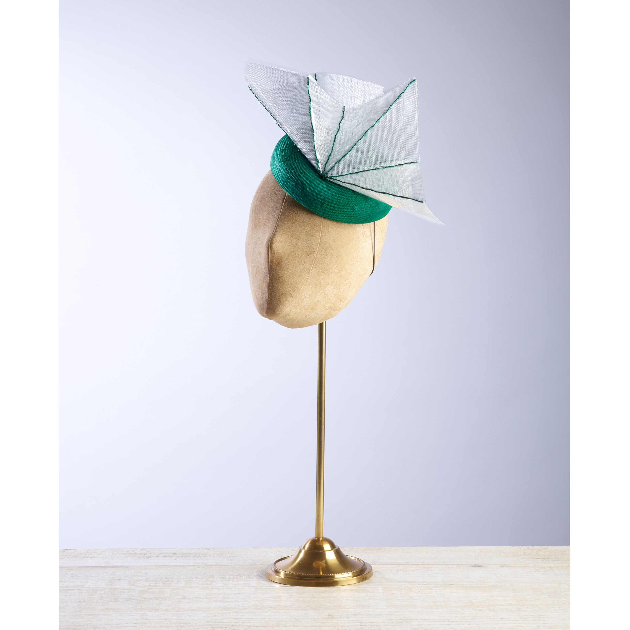 ARRIS - £70  Emerald green sisal straw button headpiece with a white and green abstract acetate fan.