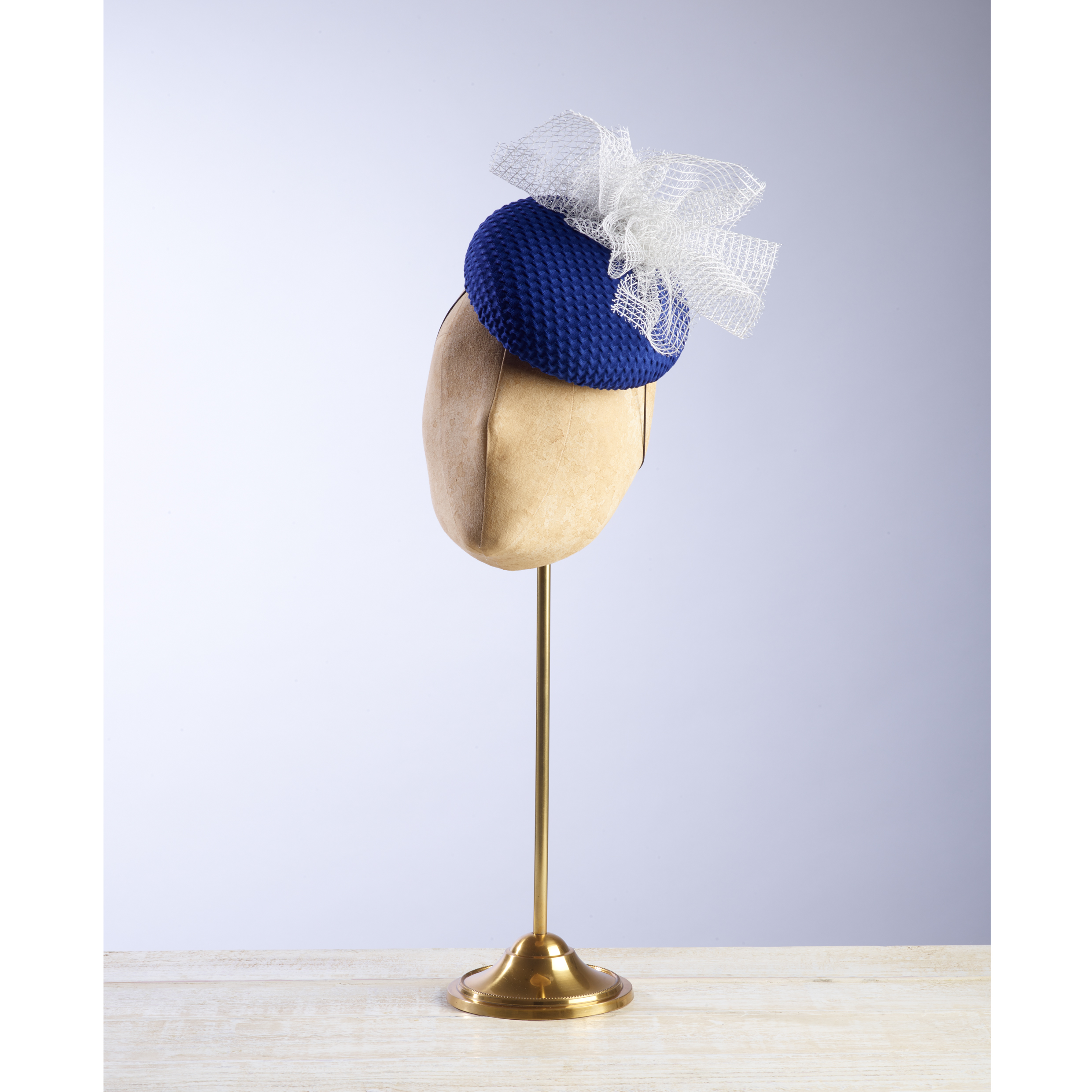 CUPOLA - £70  Royal blue fabric button headpiece with white and silver mesh spray.
