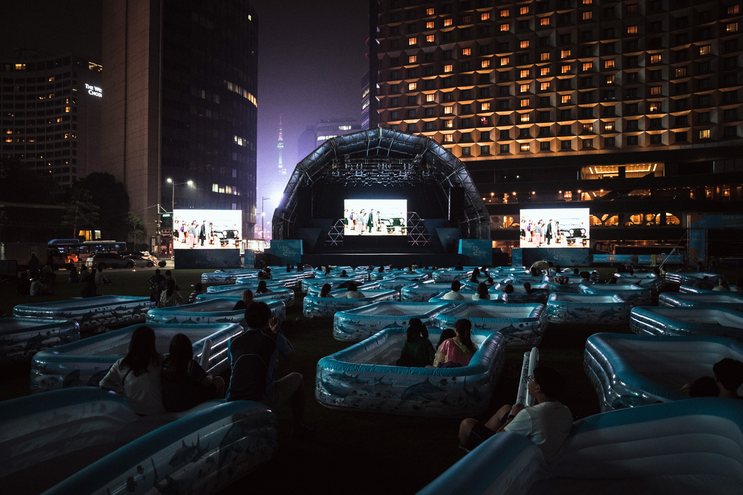 Locals sit in inflatable tubs for a film screening at the Water Festival.