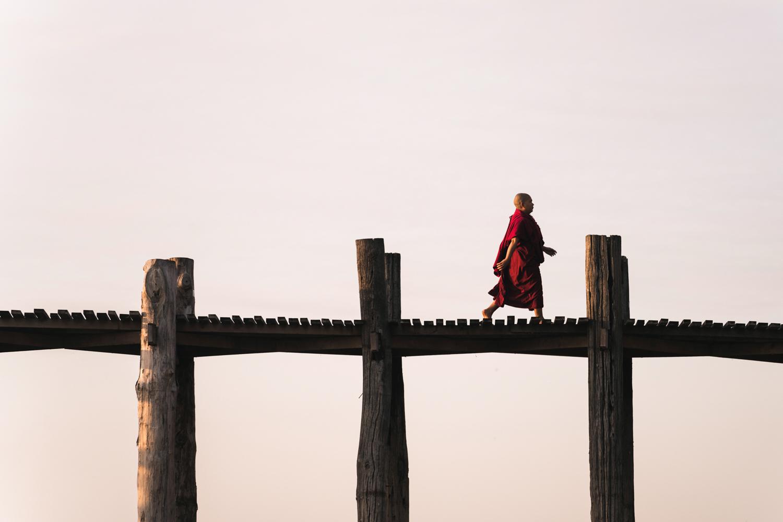 A monk walking across U Bein Bridge at sunrise.