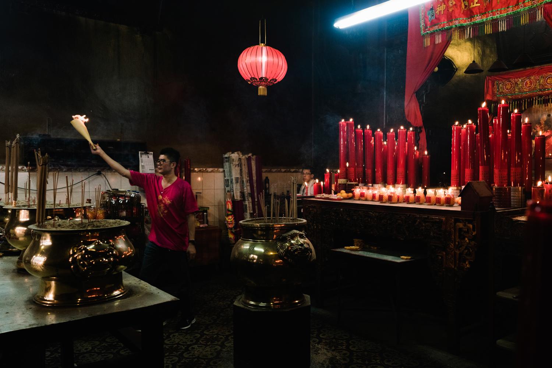 A man carries joss sticks as an offering in a Taoist temple.