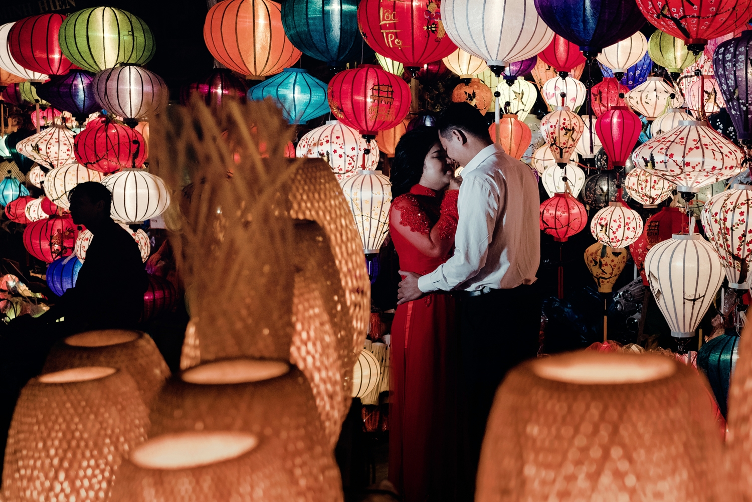 A couple embrace by the colourful Hoi An lanterns.