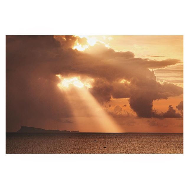 Two fishing boats crawling along at sunset, beneath the most dramatic of sun rays bursting through the almost scheduled daily storm clouds. Taken from Koh Phangan with Ang Thong Marine Park to the distance.