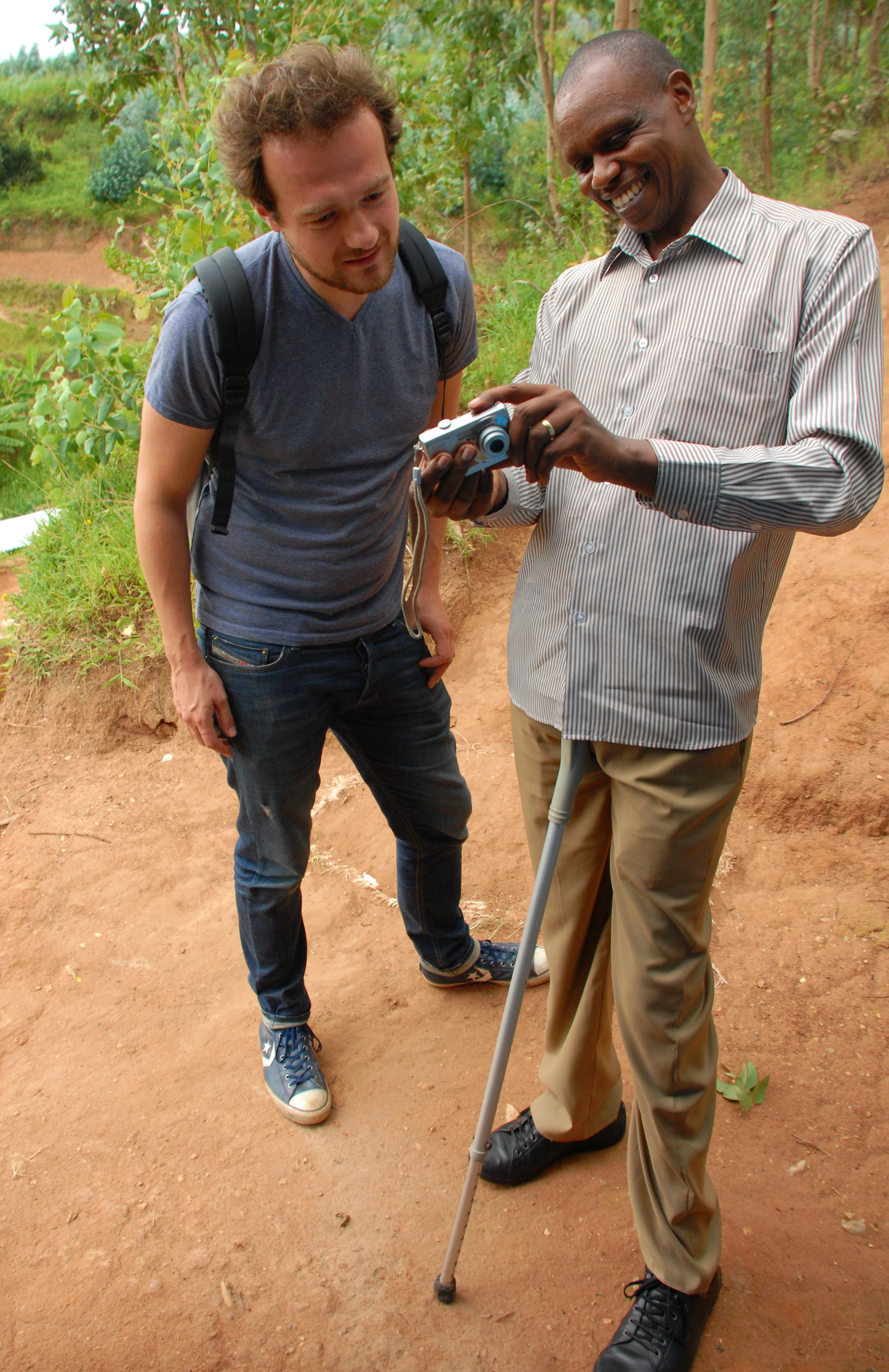 Evariste showing Lennart some pictures of smallholder farmers who received health insurance from the 2014 harvest.