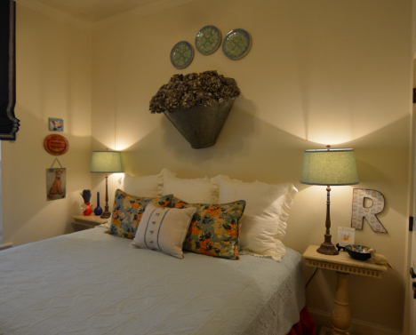 Antique plates above a bed.