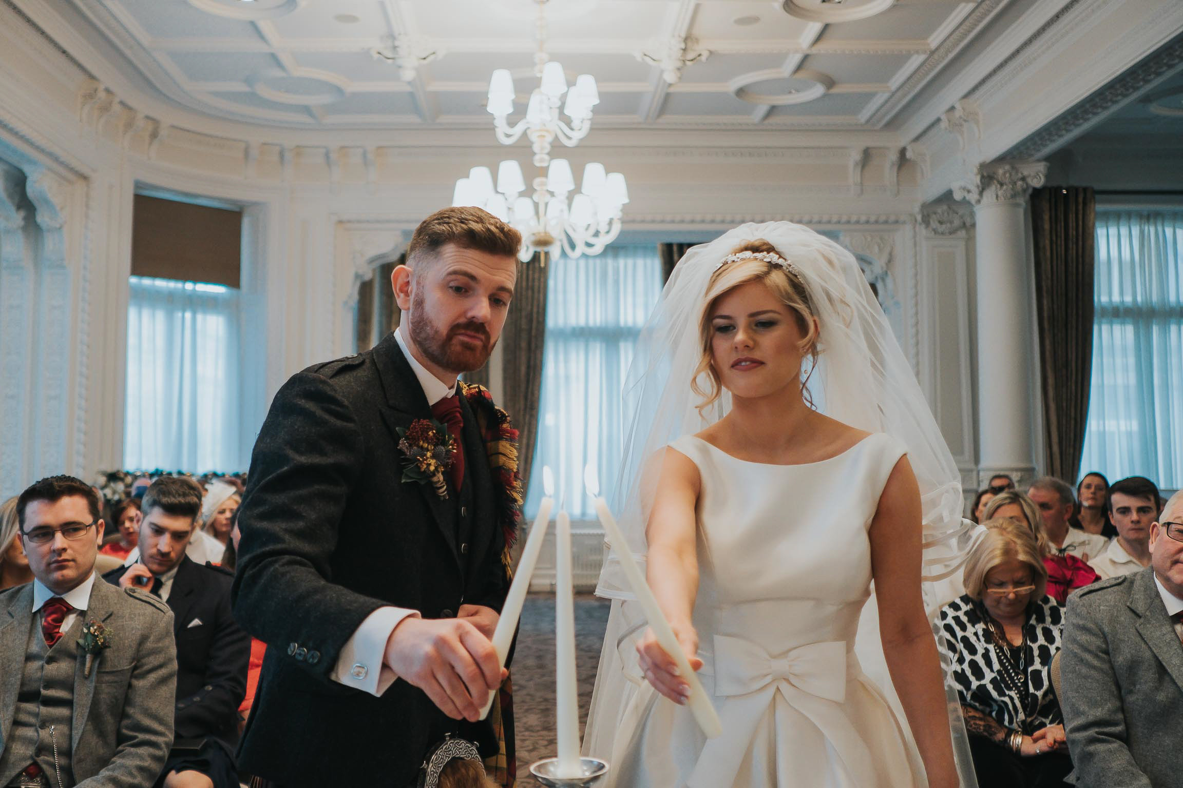 the bride and groom lighting the Unity Candle  during their wedding ceremony in Liverpool