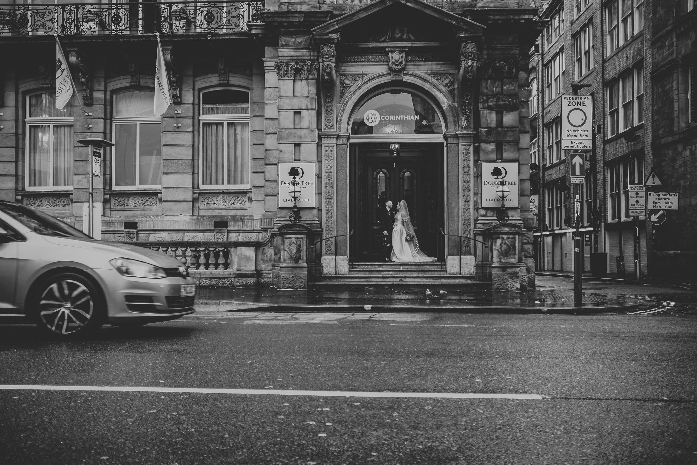 bride and groom outside the double tree in Liverpool with cars passing