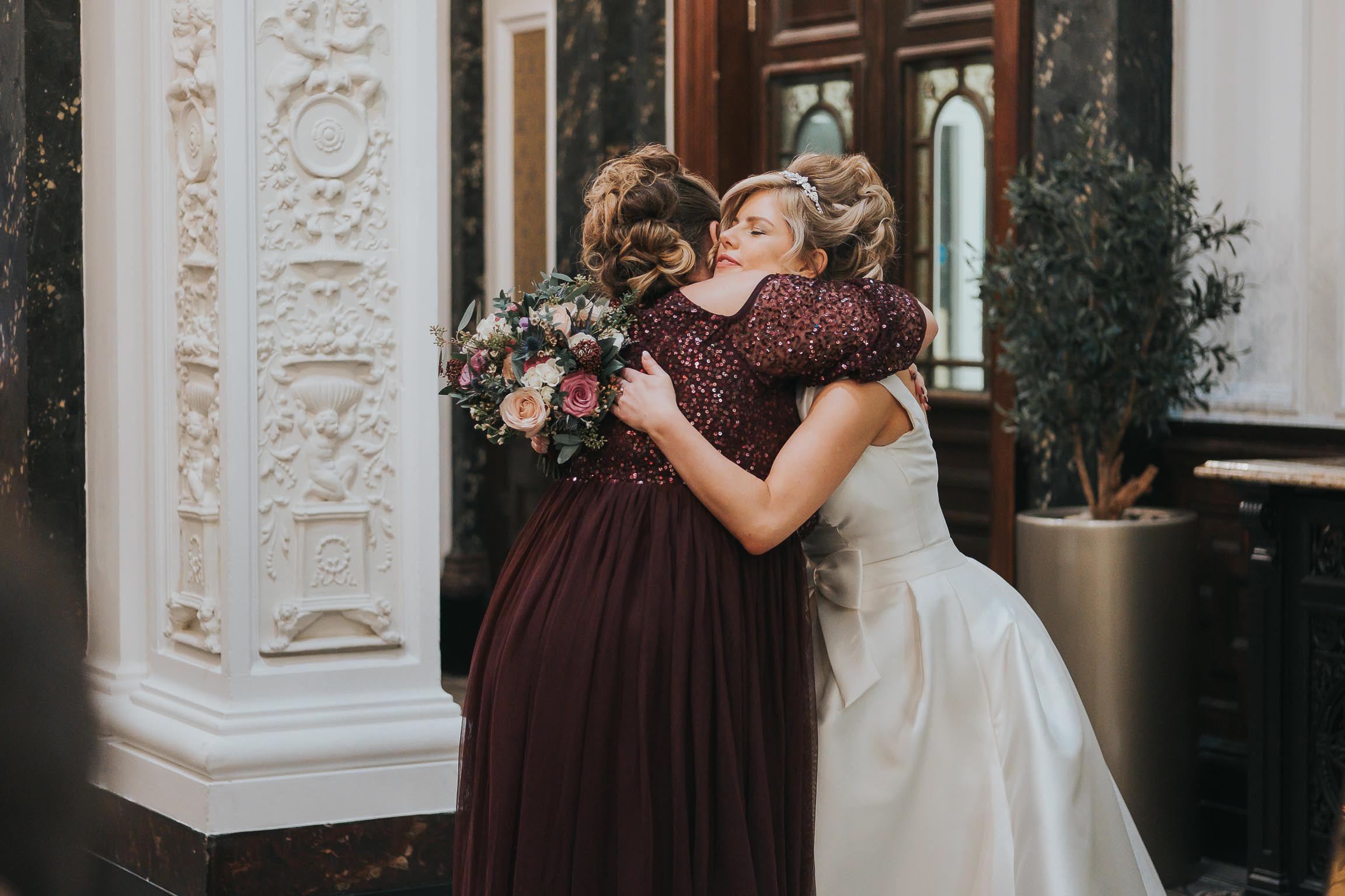 embrace by a bride and he maid of honour