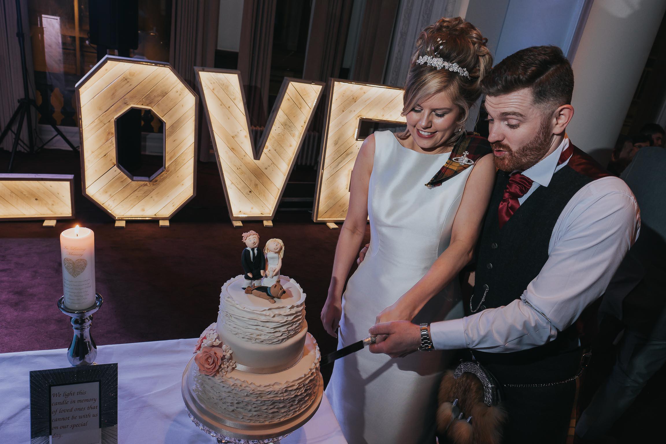 bride and groom cutting their wedding cake on their wedding day