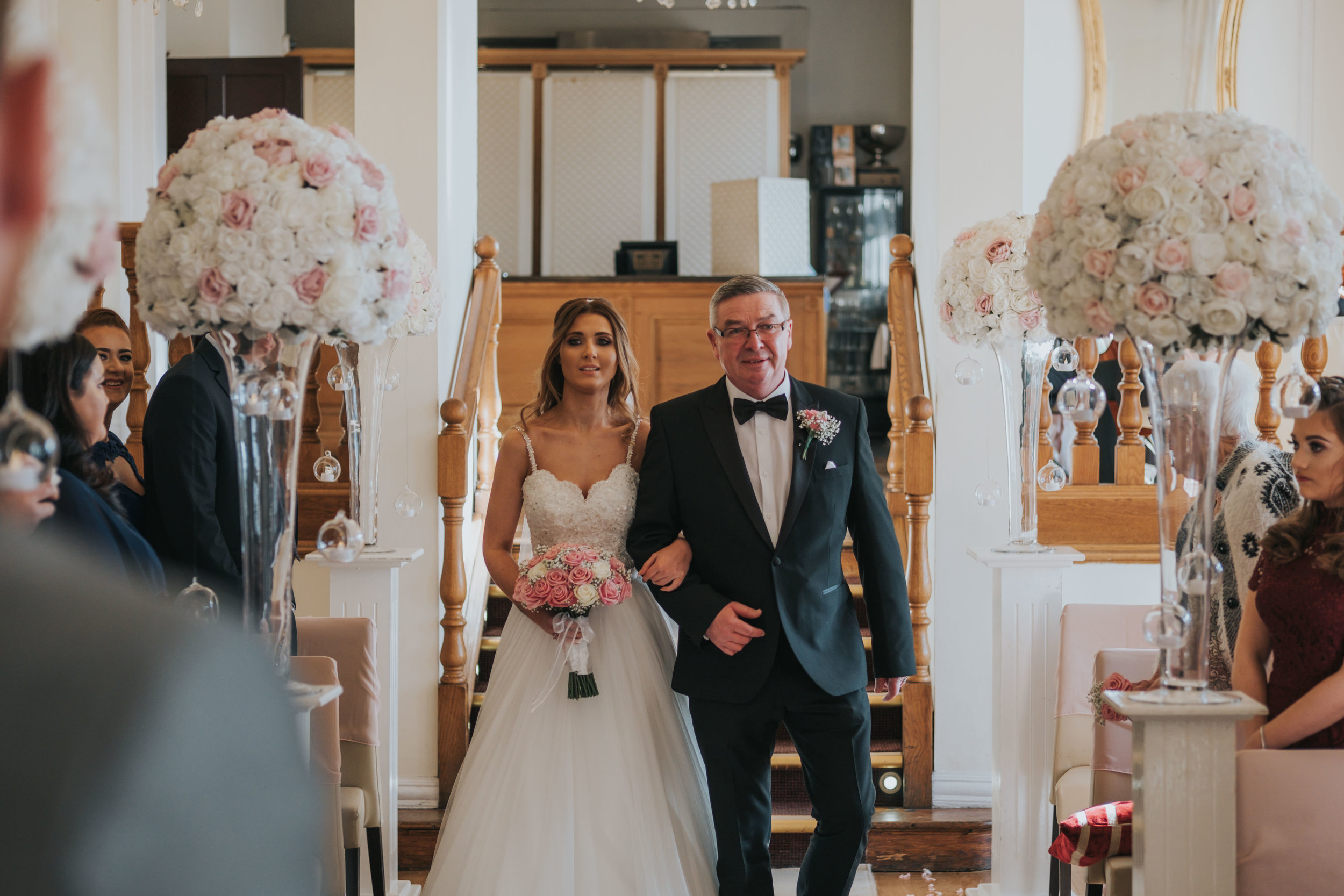 the bride and her father walking down the aisle on her wedding day at west tower exclusive wedding venue in ormskirk