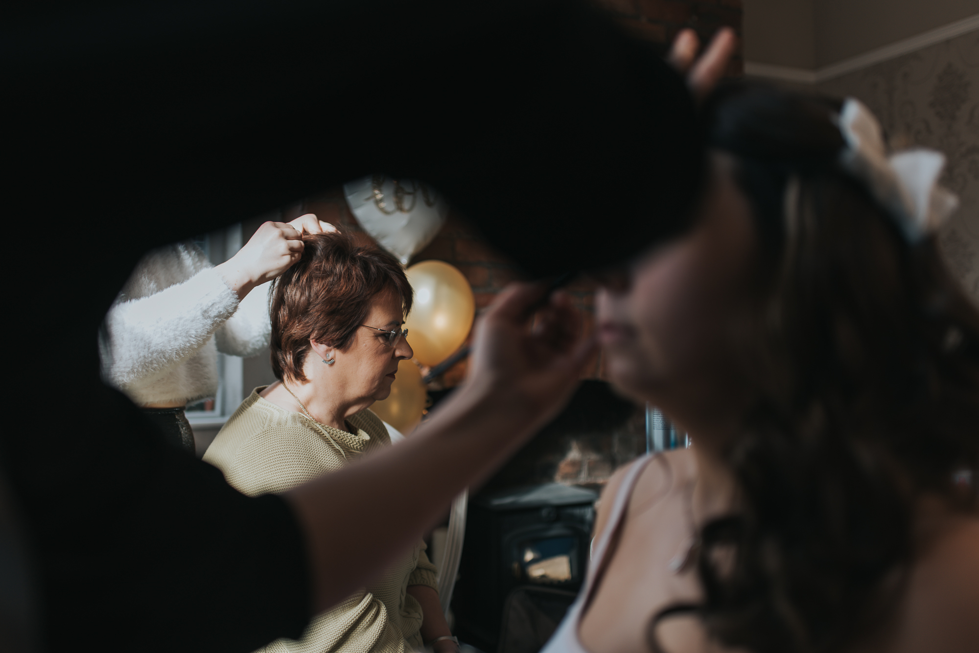mother of the bride getting her make up done before the wedding ceremony