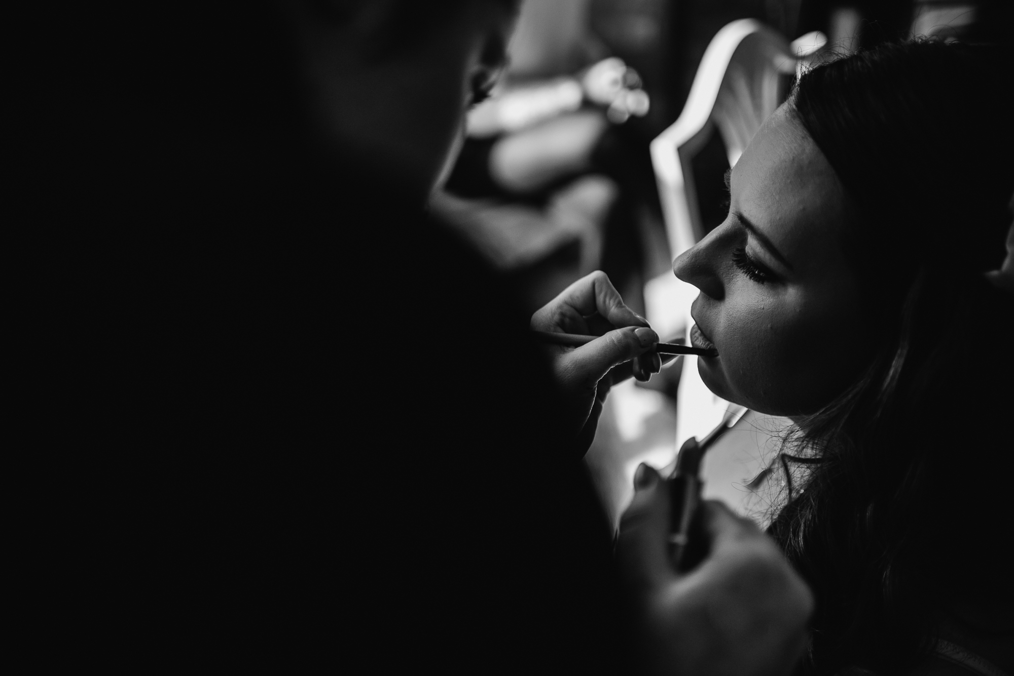 the bride on her wedding day having make up applied