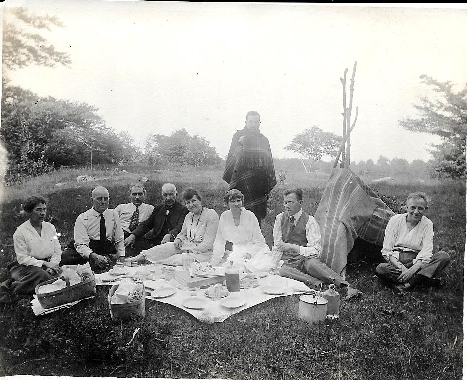 "Great-Grandpa George (standing, wrapped in a blanket) wrote on the back of this snapshot, ""Herbert  [far right, seated] -  wigwam keeper; George - Indian standing!"" This shot provides a better view of the scrumptious picnic, which looks like it involved some fluffy homemade biscuits and fried chicken. Is that cider in the glass jug?"