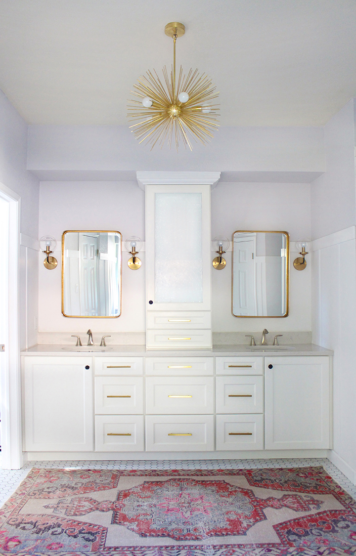 Full bathroom remodel by Kristin Laing Design with white cabinets and gold accents including a brass urchin chandelier.