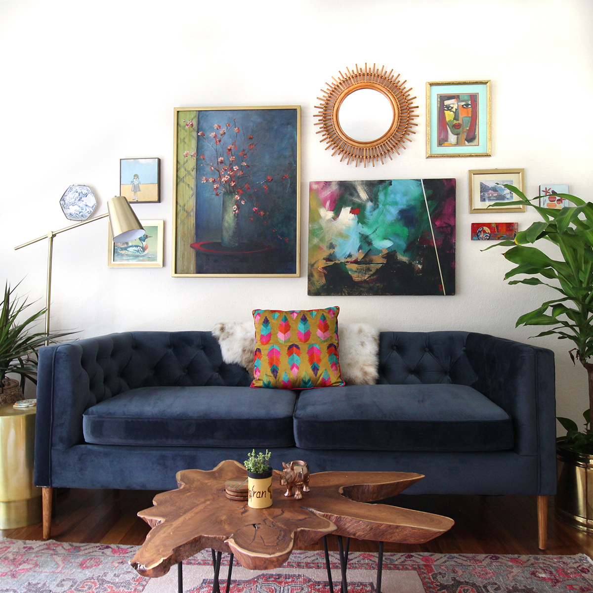 Living room featuring blue velvet sofa, live edge coffee table and colorful gallery wall by Kristin Laing Designs.
