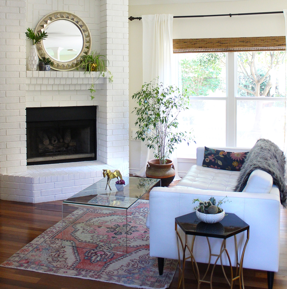 Living room by Kristin Laing Designs featuring painted brick fireplace, vintage Turkish rug and a waterfall coffee table.
