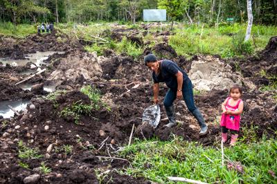 Mujer desalojada y su hija. Su vivienda fue destruida y enterrada