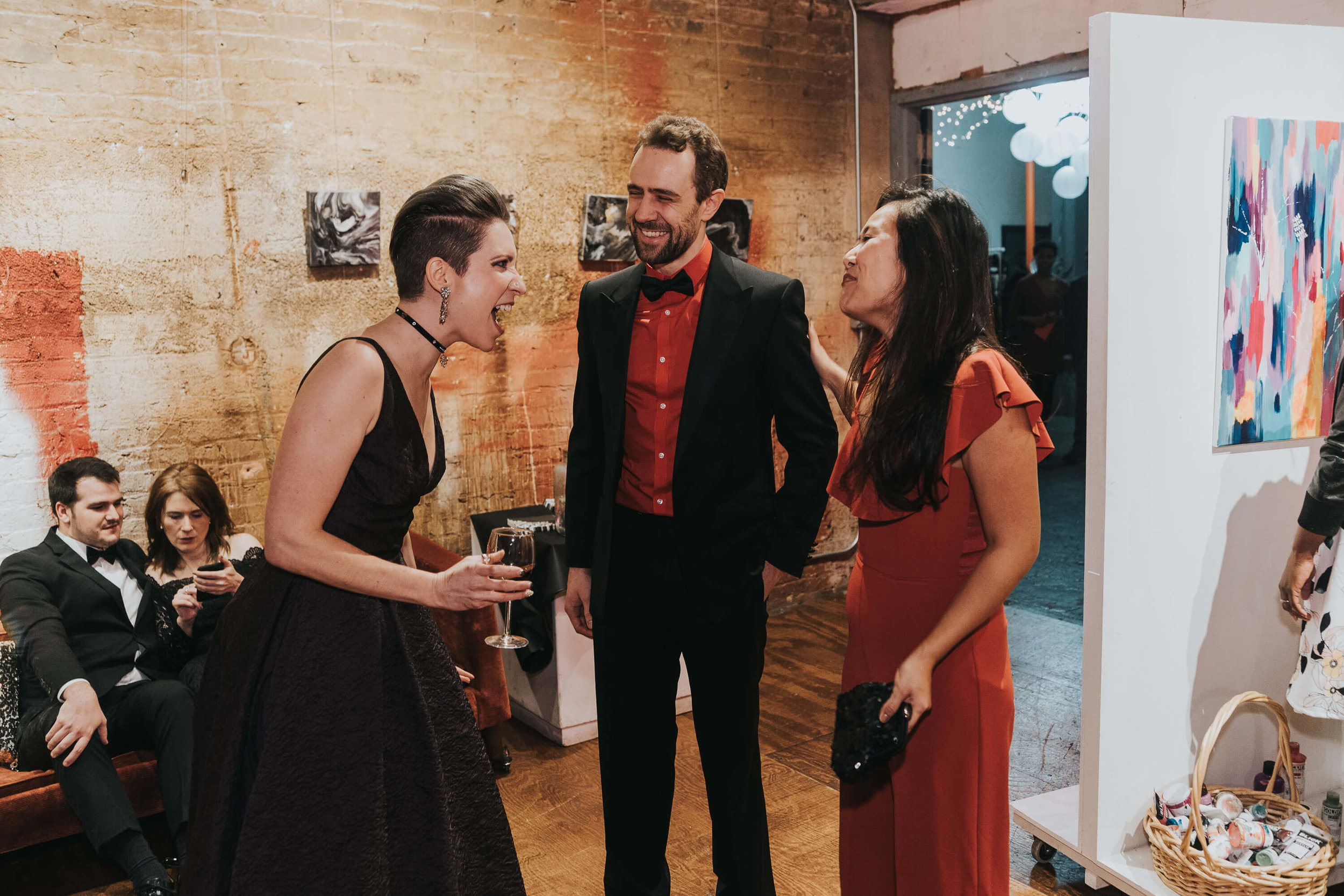 Two women and a man laughing at a party