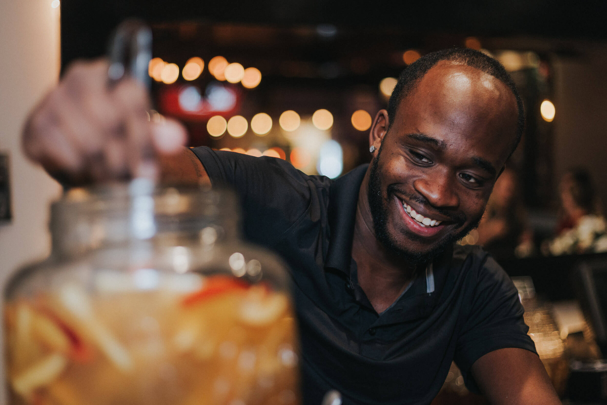 smiling man stirring a glass jar of Jack Daniels cocktail