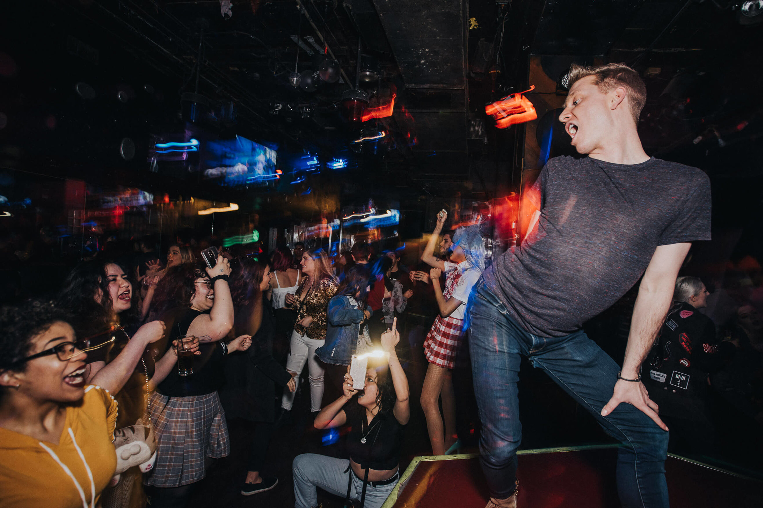 man dancing on platform in crowded night club