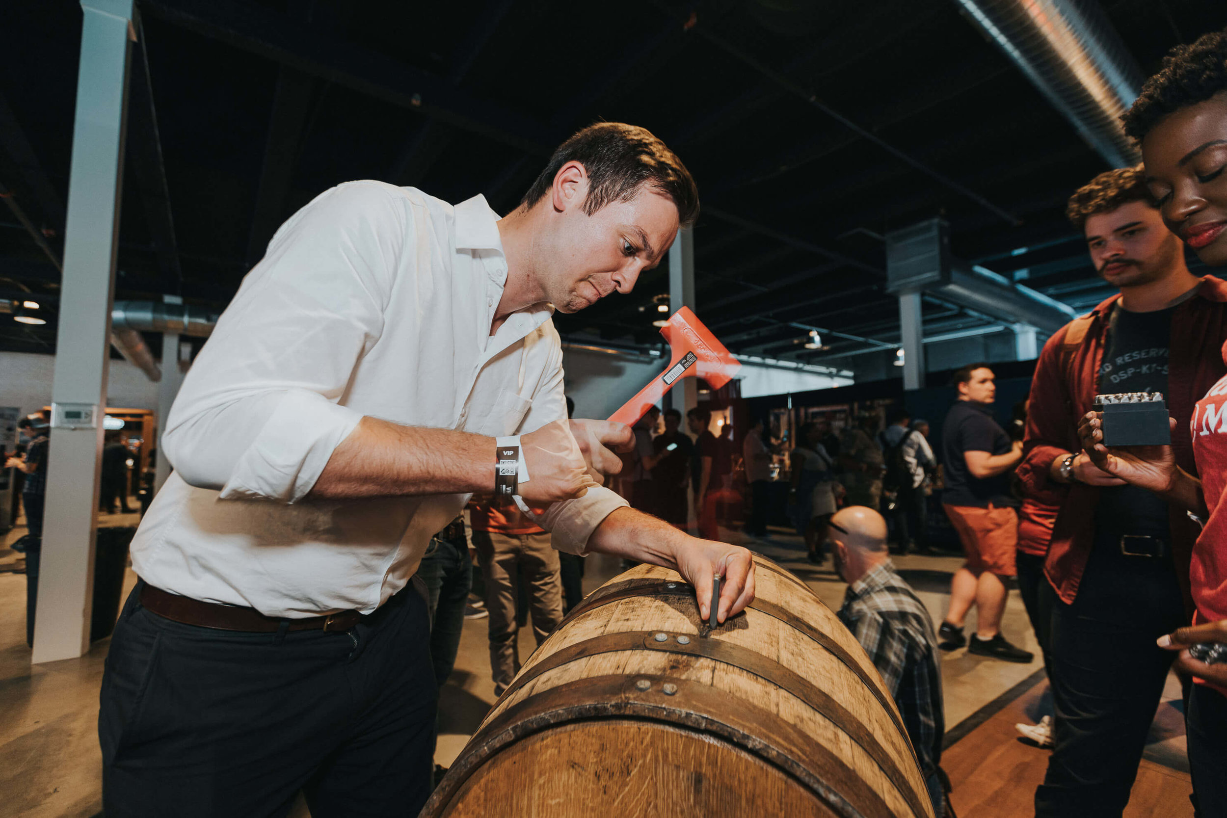 man hammering nail into barrel at whisky event