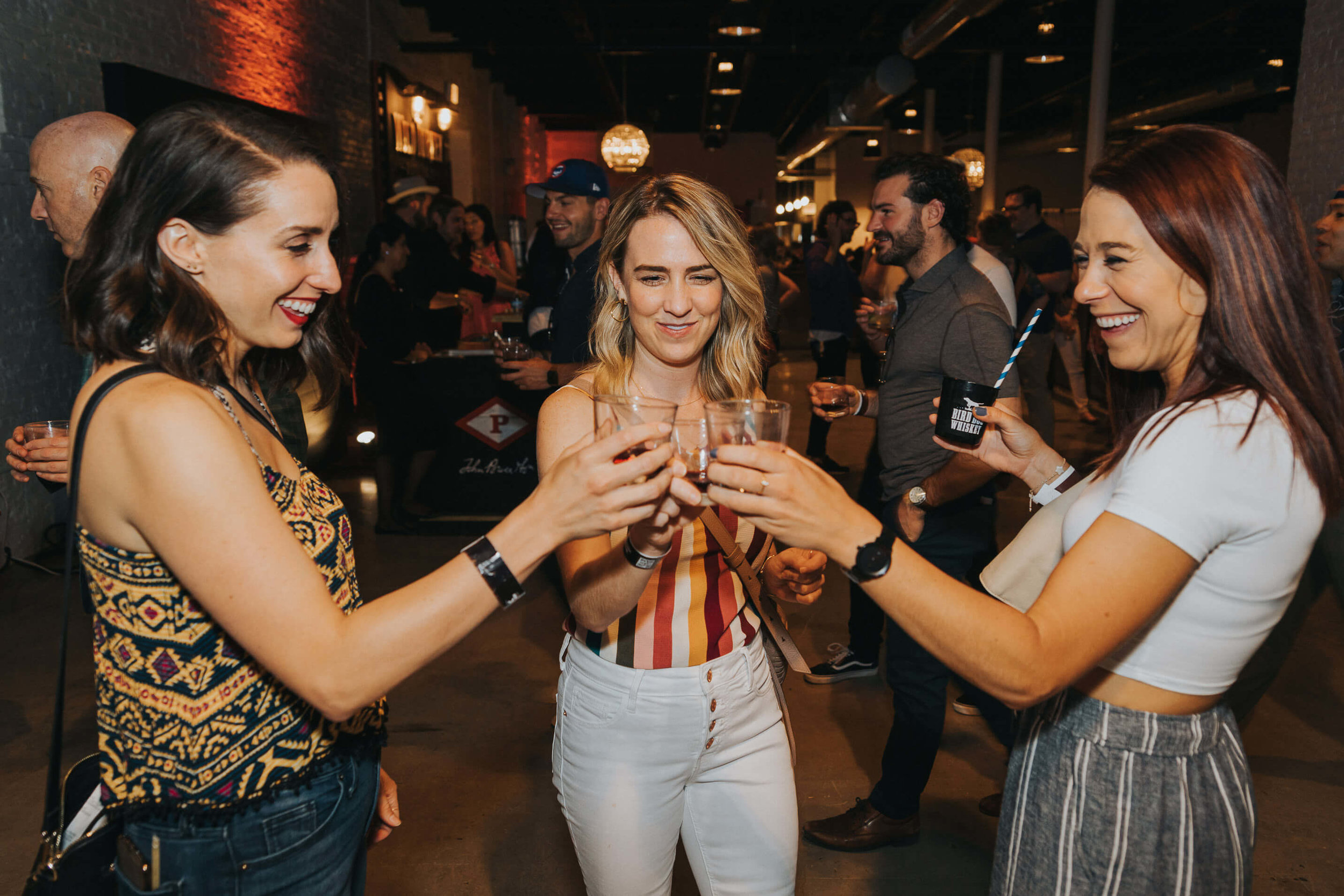 three young women cheers at whisky event