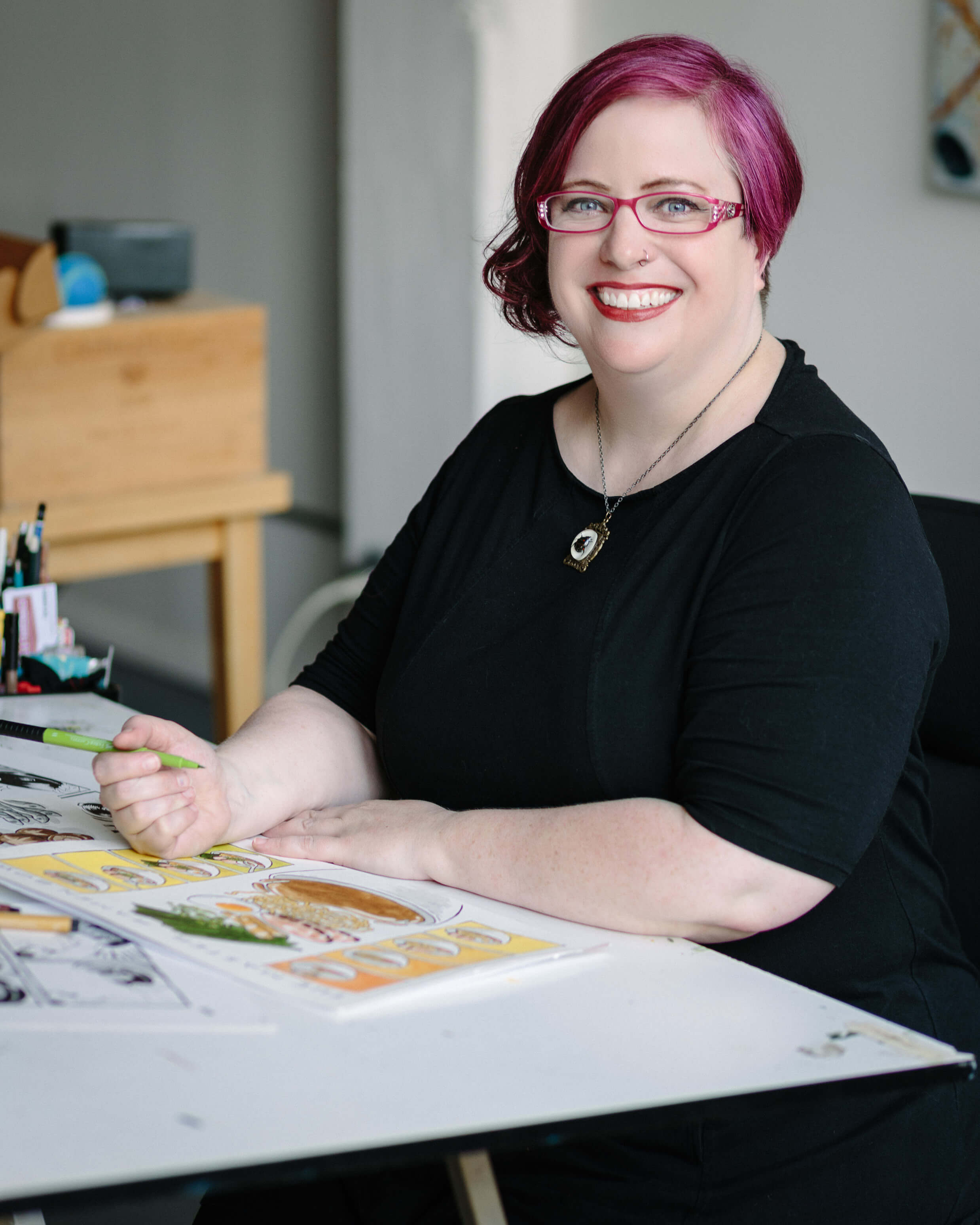 female illustrator smiling at desk