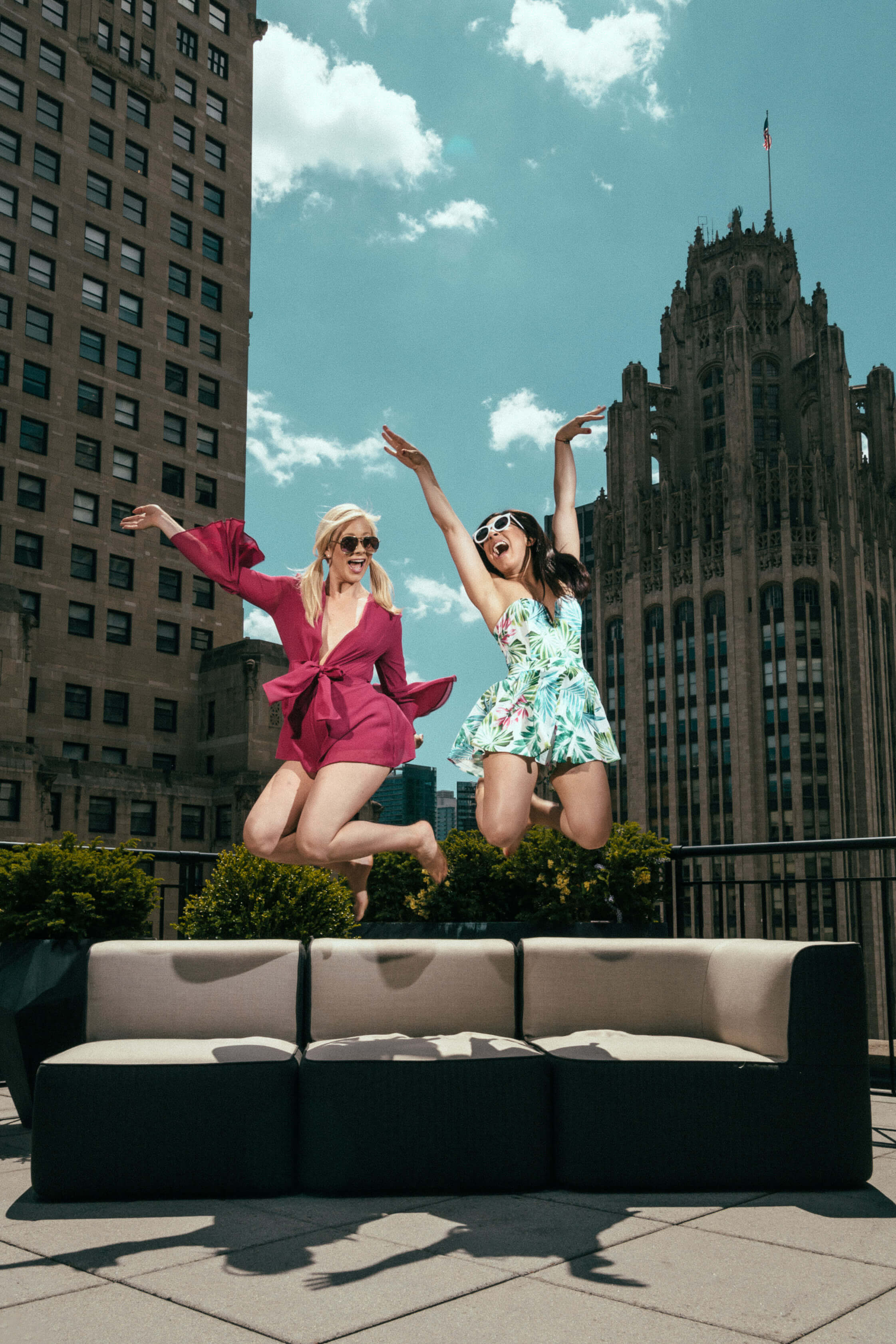 two female bloggers jumping in the air cheering
