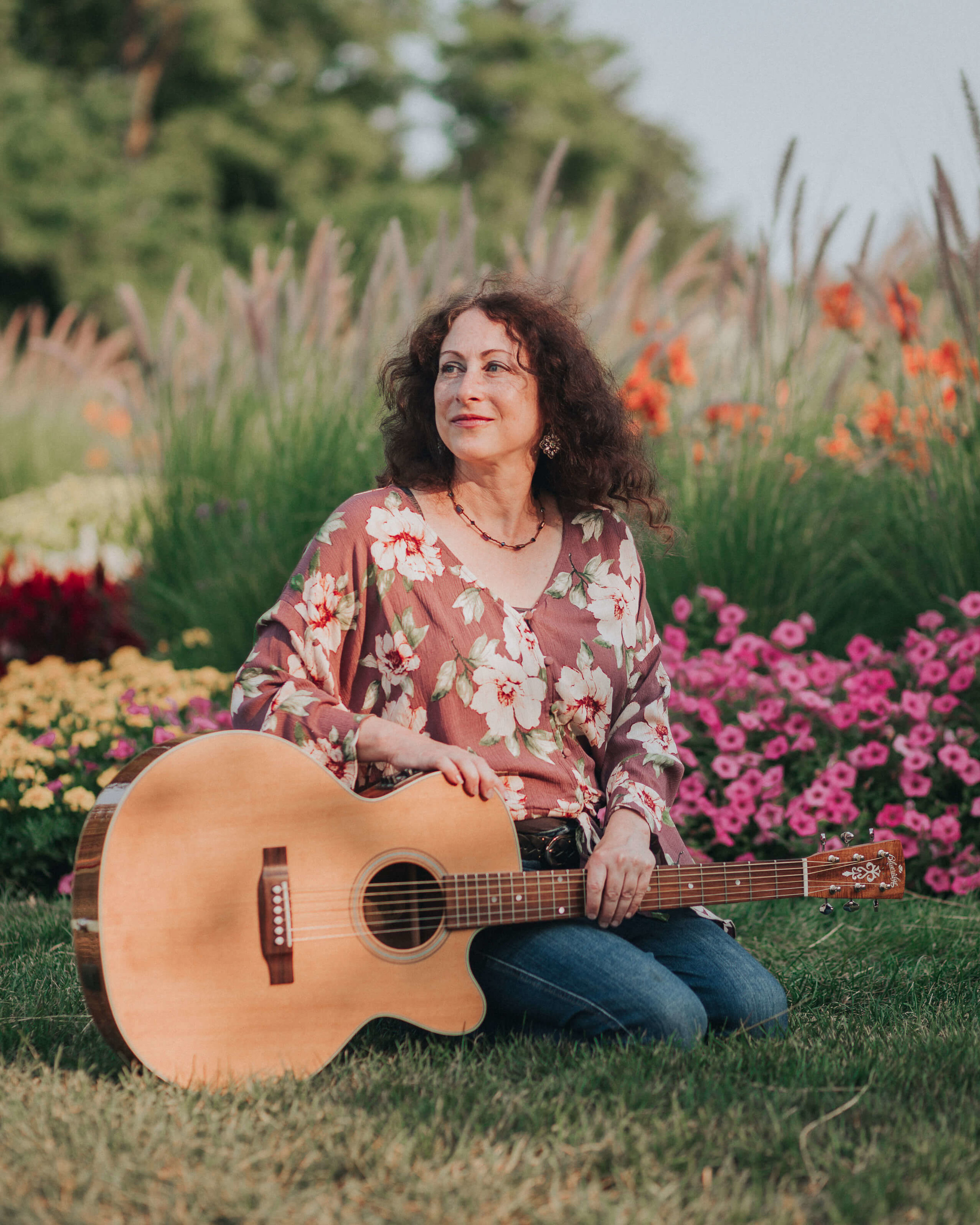 female musician near flowers with acoustic guitar