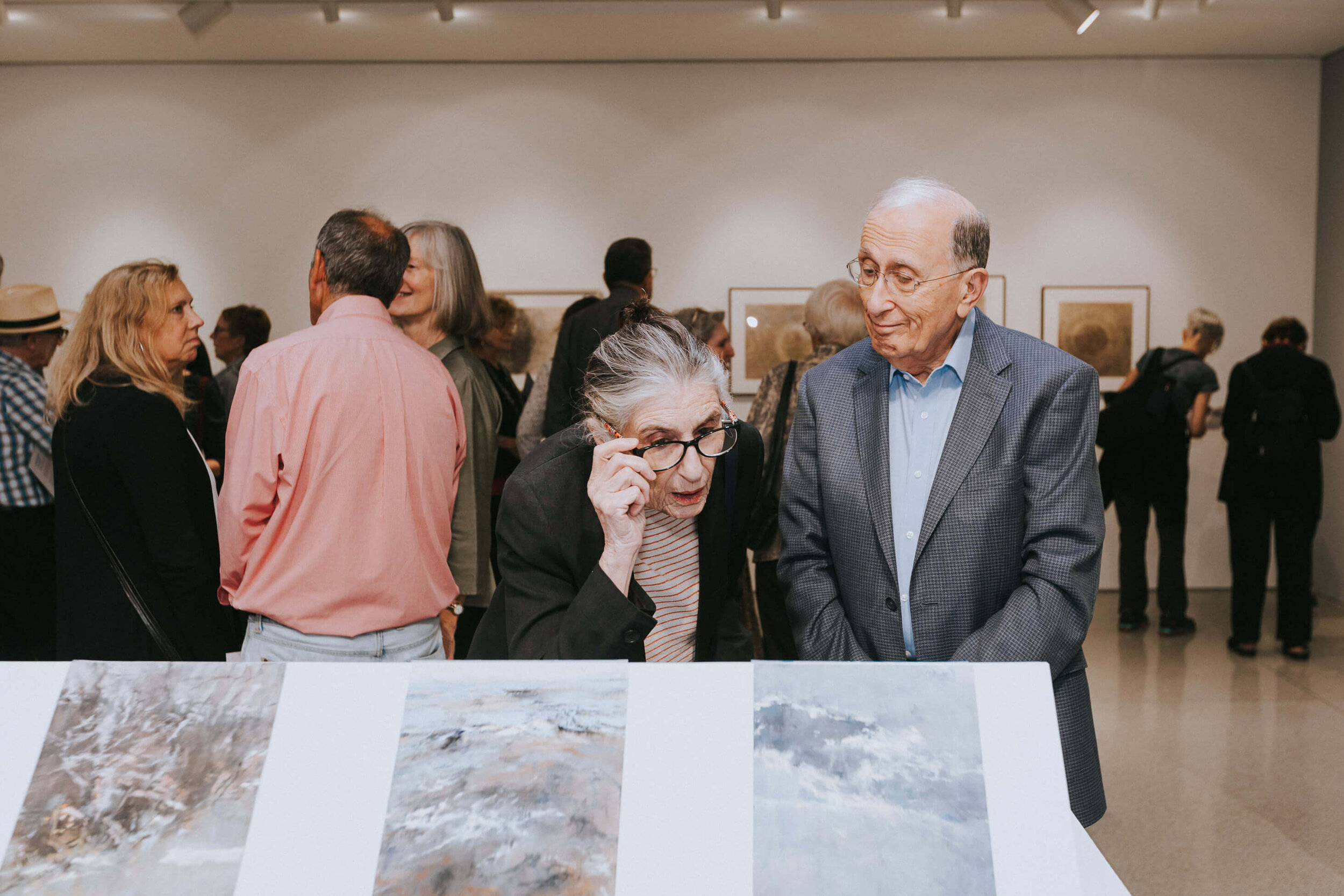 Man and woman examining art at Chicago gallery opening