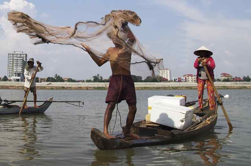 Fisherman and his wife on a small wooden boat on the Mekong river, Phnom Penh