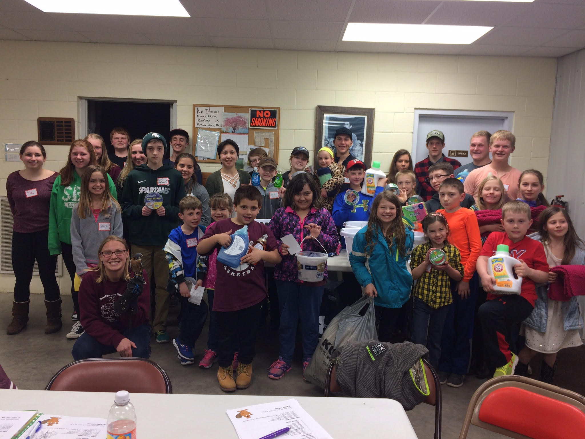 The Antigo 4-H donated supplies to REGI at one of their April 2017 meetings. The group poses with Director of Education, Elise, and Benji the American Kestrel.