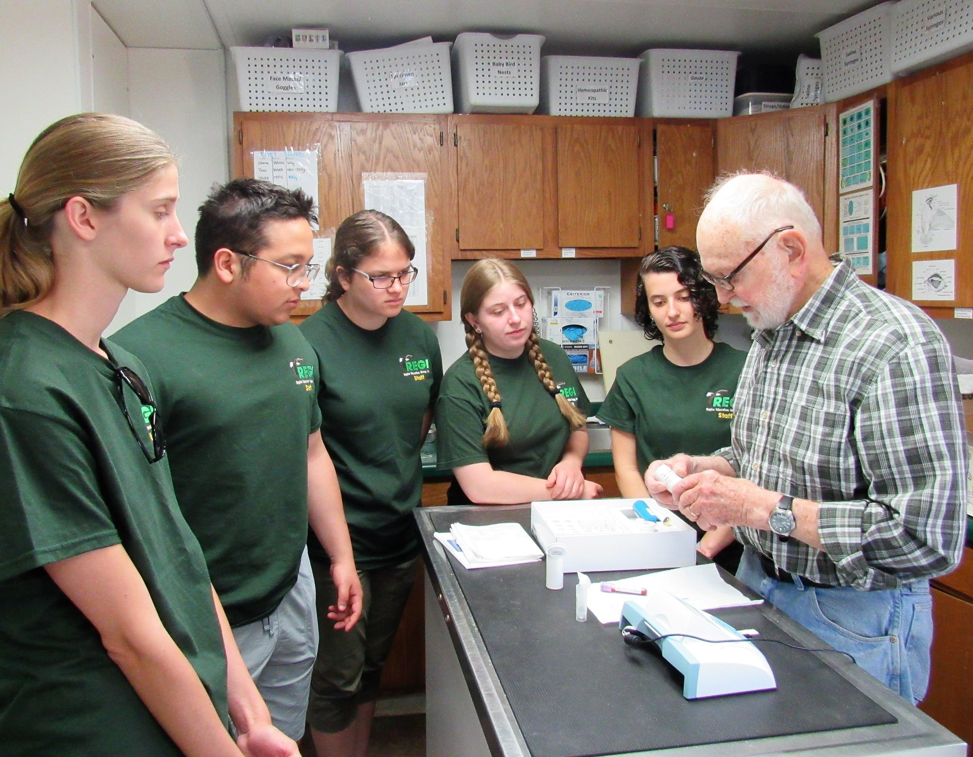 Don Gibson testing the eagles blood for lead poisoning with the interns observing.