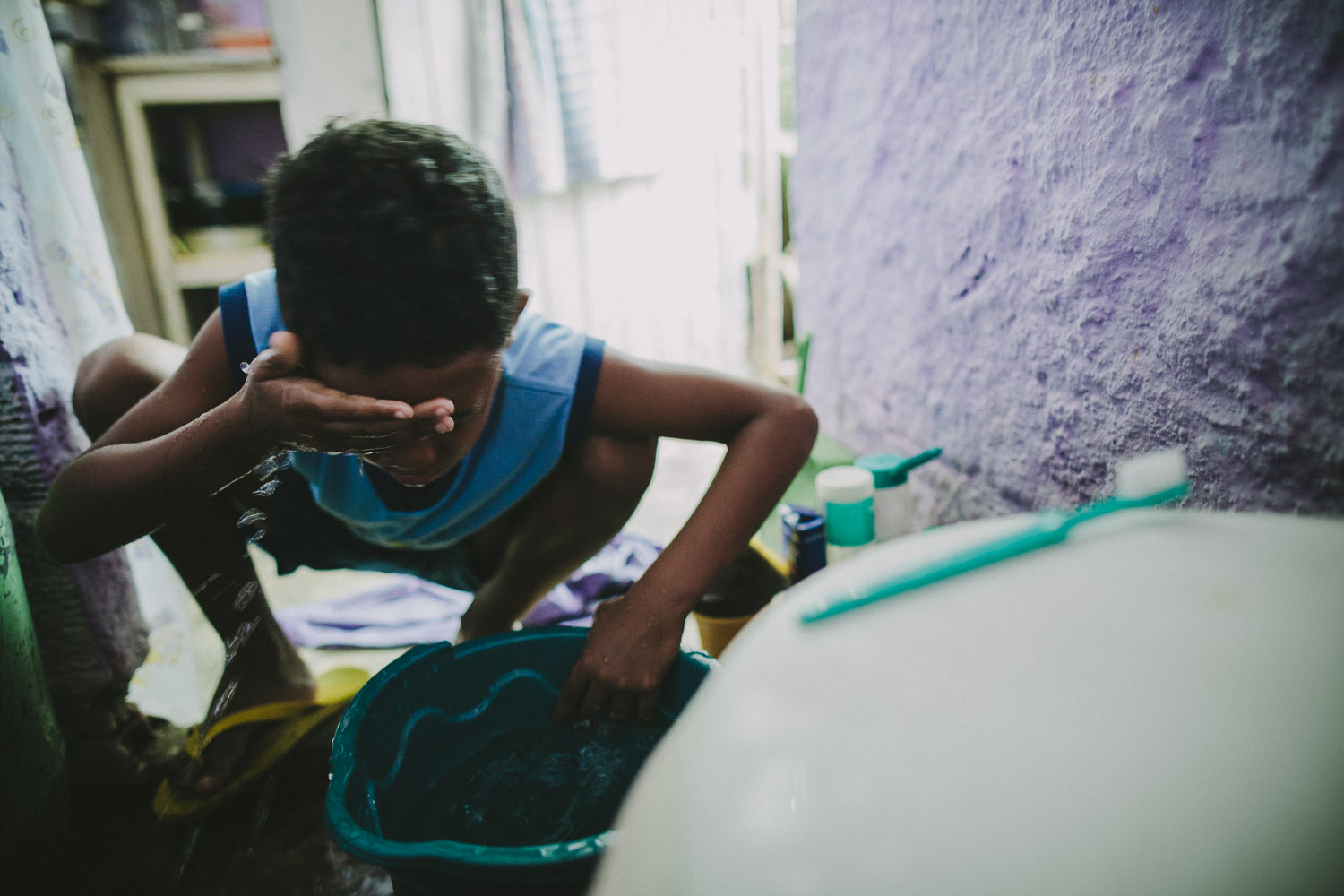 The space where Emidio washes his face in the morning is the same space where the family does all their bathroom, kitchen, and sleeping activities. Emidio's entire house (housing 4 people---soon to be 5) is perhaps no larger than 8 feet by 10 feet. This is Emidio's morning routine before heading to classes at the Compassion Center.