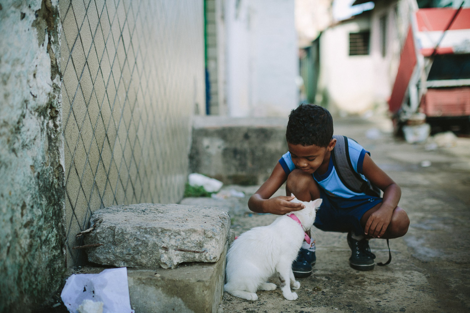 Emidio is very playful and on the way to school he spots a cat and takes the time to play with it. Emidio walking to his classes at the Compassion Center.
