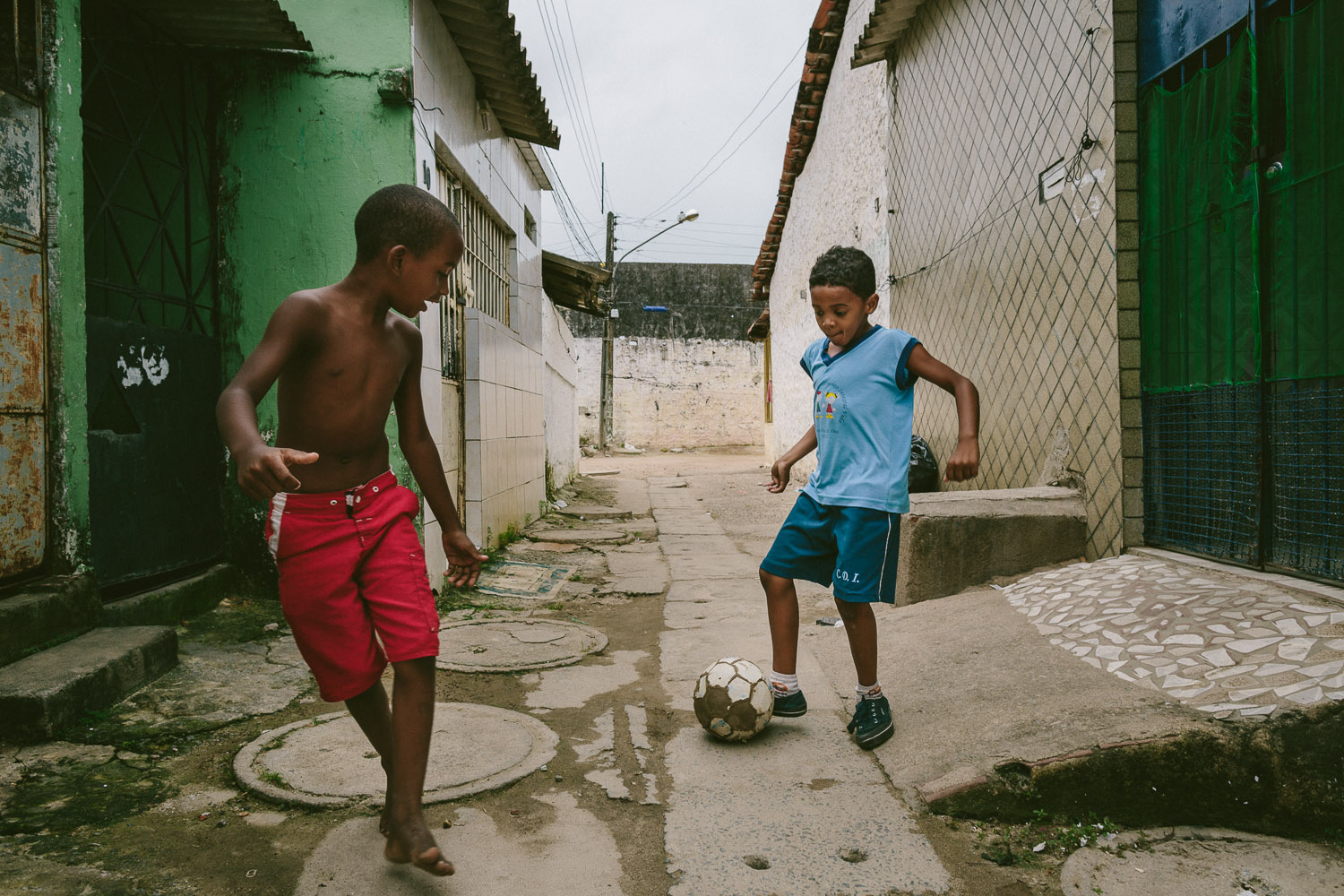 """On the way home, Emidio's friend spots him and asks if he wants to pass the ball around while he walks home. Soccer is the most popular sport in Brazil and home to the 2014 World Cup. After his time at the Compassion Center, Emidio walks to his """"aunt's"""" house (family friend---no relation) to be taken care of before heading to school since his mother works until 10pm each night."""