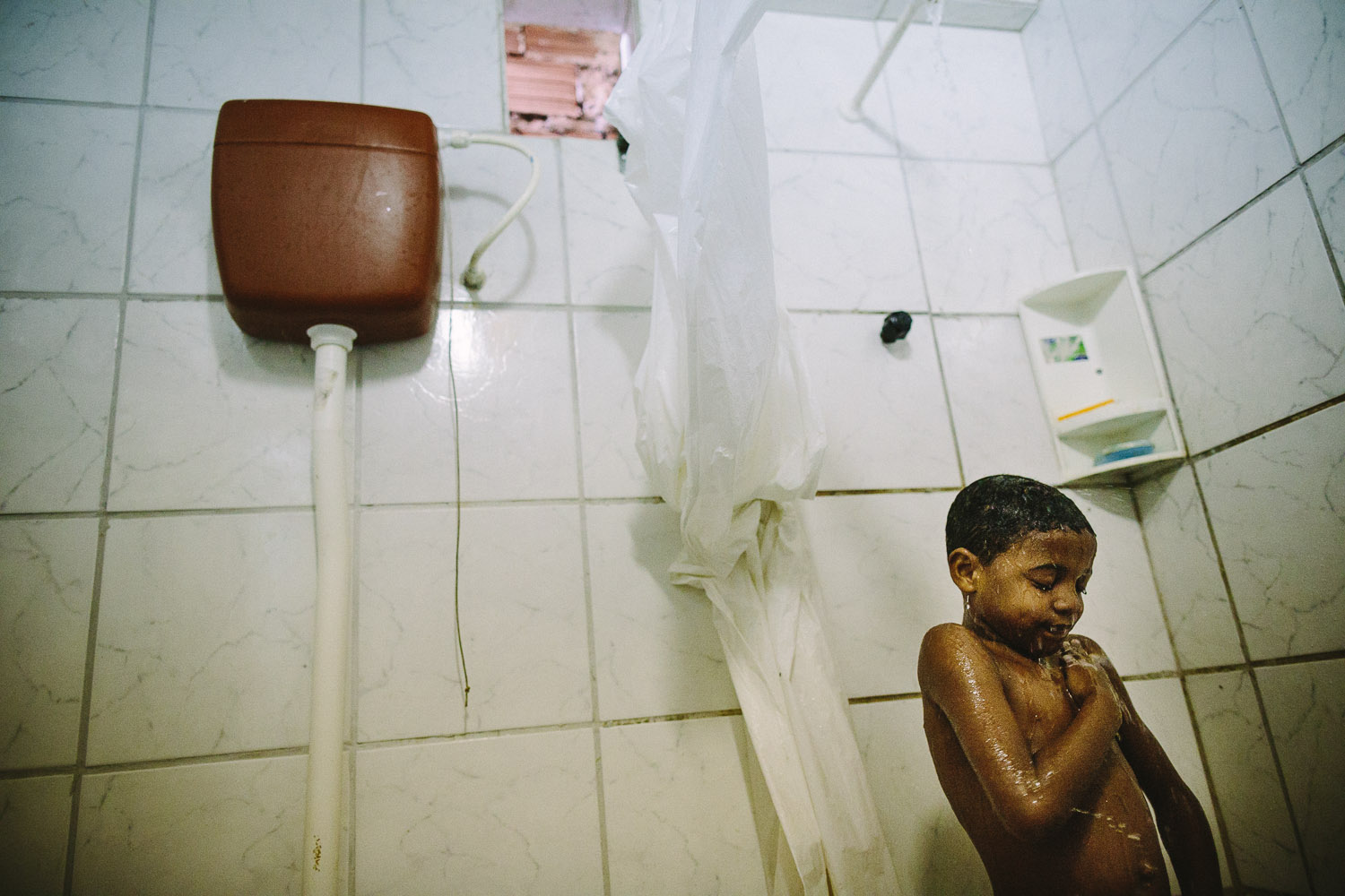 "Even though Emidio is poor by our standards the joy of a cool shower is universal. Each day an ""aunt"" (family friend--relation) takes care of Emidio and his younger brother between his time at the Compassion Center and School since his mother works until 10pm at night."